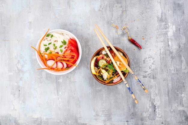 Salada picante asiática de macarrão de vidro ou funchoza com salada de cenoura e legumes em fundo de pedra