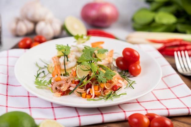Salada picante com camarão em um prato branco. comida tailandesa.