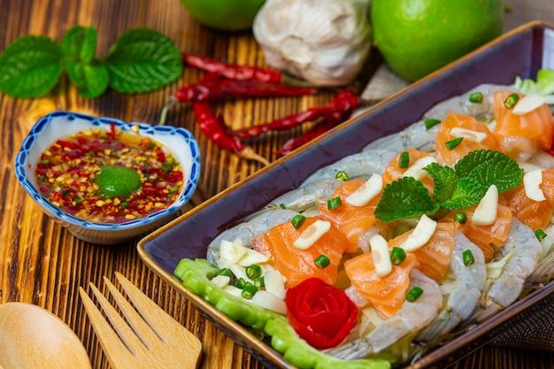 Salada picante de camarão e salmão em superfície de madeira