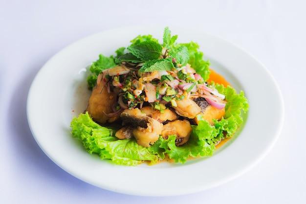 Salada picante de peixe-gato picada com ervas na festa