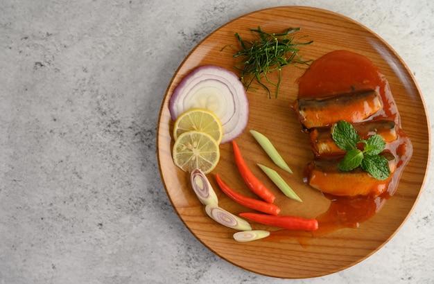 Salada picante de sardinha em molho de tomate na bandeja de madeira