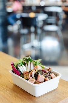 Salada picante do presunto fumado cortado grosso com azeitonas pretas na tabela de madeira com fundo do borrão.