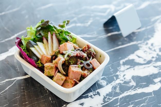 Salada picante do presunto fumado cortado grosso com azeitonas pretas no tampo da mesa de mármore.