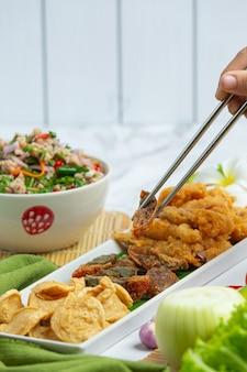 Salada picante mista com linguiça vietnamita, ovos em conserva e lulas crocantes, comida tailandesa.