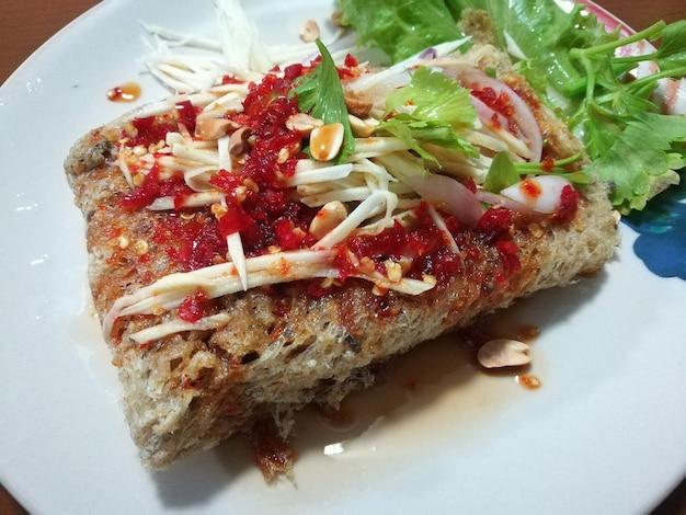 Salada picante peixe-gato crocante com fatia de manga comida gostosa quente