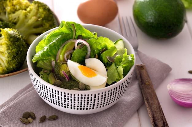 Salada preparada com folhas verdes frescas, cebola e ovo cozido de frango