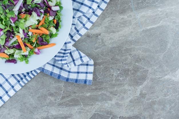Salada preparada com legumes frescos, no prato, na toalha, na mesa de mármore.
