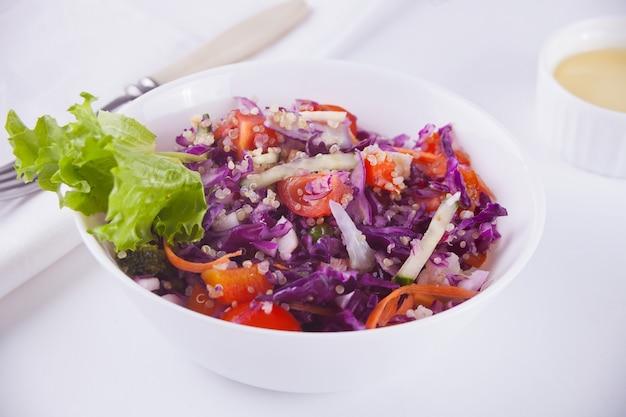Salada primavera com repolho roxo, rabanetes, tomate, cebola na tigela branca
