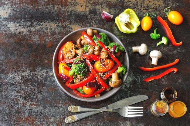 Salada quente com brócolis, cogumelos e pimentão vermelho. tigela vegetariana com legumes quentes em um elegante fundo gasto. comida saudável. almoço de fitness com cogumelos e legumes.