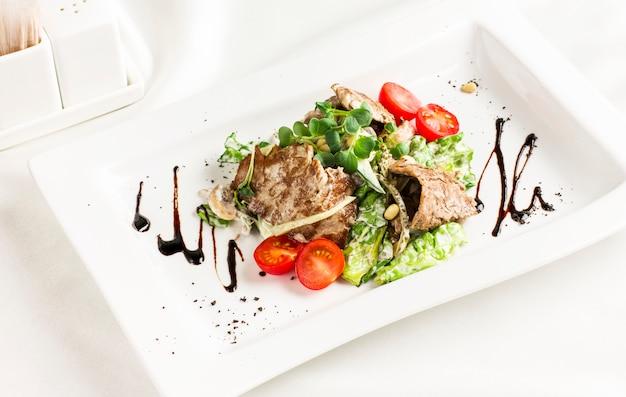Salada quente com carne, cogumelos, tomates cereja, pinhões e ervas
