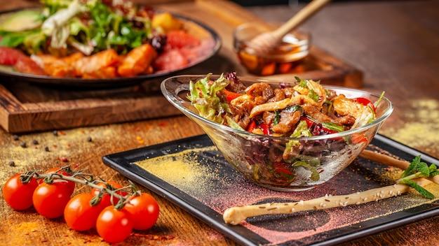 Salada quente com carne e frango, pimentão e molho de hortelã mel.