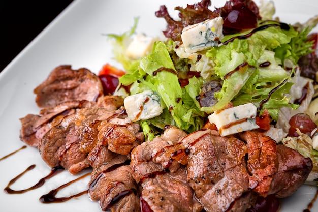 Salada quente com carne e queijo em um prato branco