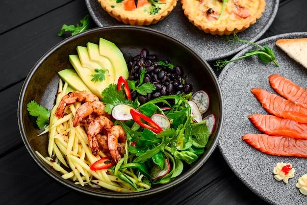 Salada quente com marisco grelhado na horizontal. vista superior do prato com mix de camarões assados