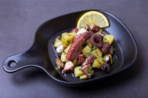 Salada quente com polvo, batata e limão numa pequena frigideira preta. close-up, fundo preto.