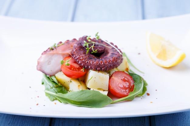 Salada quente com polvo, batata, tomate cereja, microgreens de rúcula e limão em um prato branco