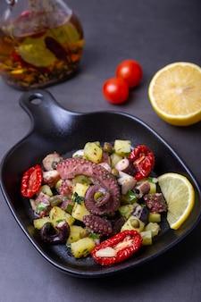 Salada quente com polvo, batata, tomate seco, alcaparras e limão em uma panela preta pequena. close-up, fundo preto.