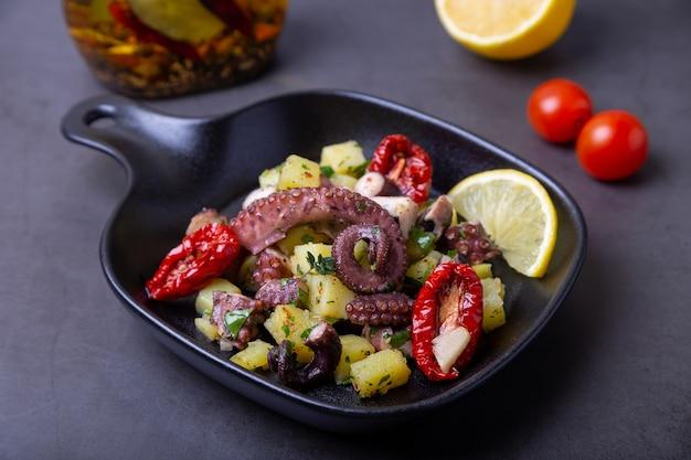 Salada quente com polvo, batata, tomate seco, alho e limão em uma pequena frigideira preta. close-up, fundo preto.