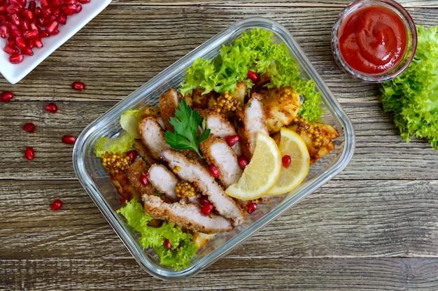 Salada quente de batatas assadas, carne, verduras com molho picante em uma tigela de vidro em uma mesa de madeira. lancheira. vista do topo.