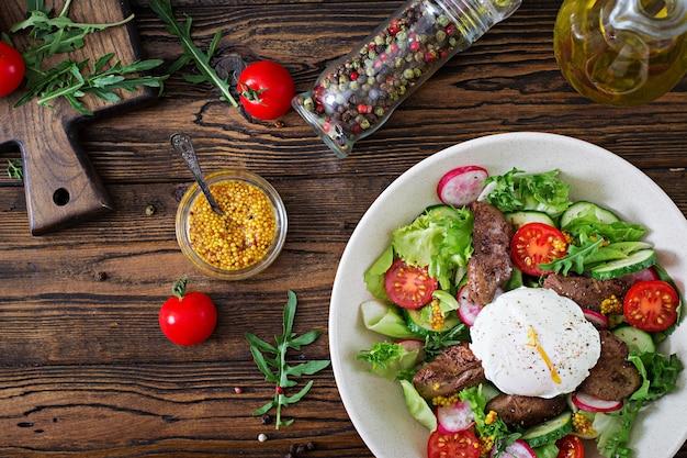 Salada quente de fígado de frango, rabanete, pepino, tomate e ovo escalfado. comida saudável. topo