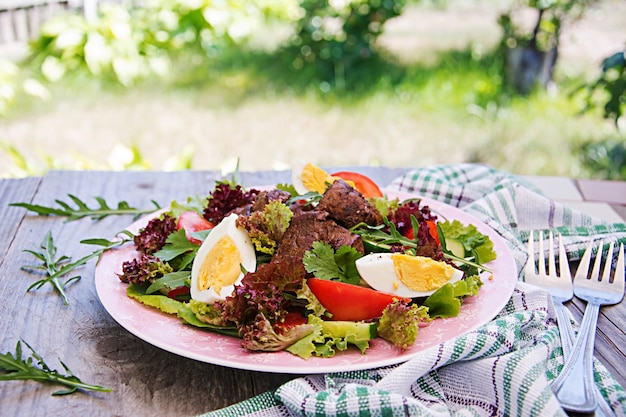 Salada quente de fígado de frango, tomate, pepino e ovos. jantar saudável. cardápio dietético