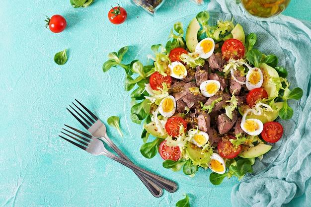 Salada quente de fígado de galinha, abacate, tomate e ovos de codorna. jantar saudável. cardápio dietético. postura plana. vista do topo