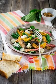 Salada quente de outono com batatas, cogumelos, bacon, espinafre, molho de mostarda e queijo em um guardanapo de laranja. superfície de madeira velha. foco seletivo.
