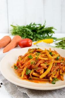 Salada quente picante de feijão verde com molho de tomate no prato na mesa de madeira branca