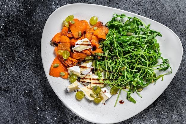 Salada quentinha grelhada com rúcula, nozes e queijo brie. fundo preto. vista do topo.