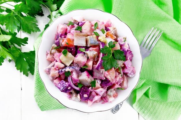 Salada rosoli finlandesa com arenque, beterraba, batata, pepino em conserva ou em conserva, cenoura, cebola e ovos, temperada com maionese em uma tigela contra uma placa de madeira de cima