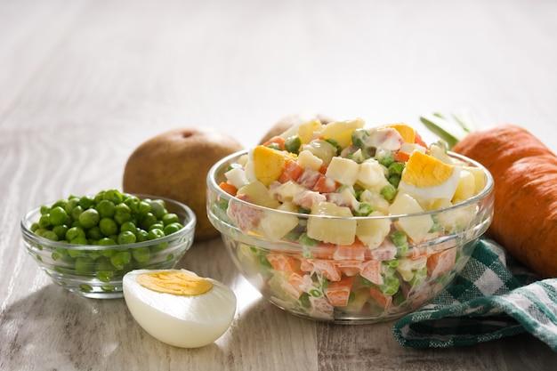 Salada russa tradicional e ingredientes, salada de olivier na mesa de madeira.