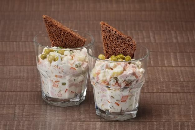 Salada russa tradicional olivier com ervilha em vidro