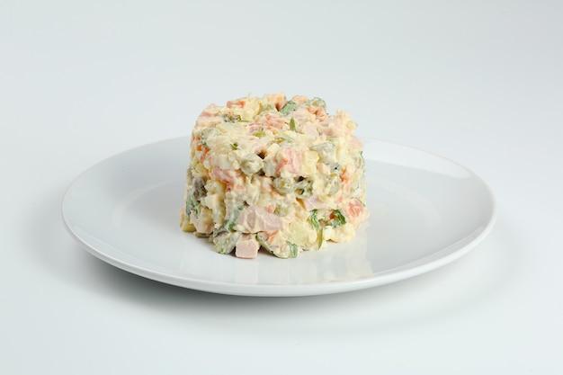 Salada russa tradicional olivier de legumes cozidos e carne com molho na tigela. ano novo russo ou natal isolado no branco.