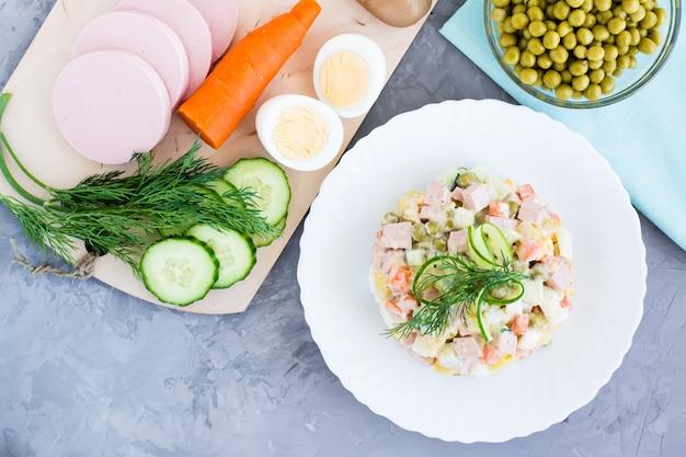 Salada russa tradicional olivier em um prato e ingredientes para a sua vista superior preparationin
