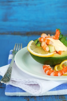 Salada saborosa com camarão e abacate no prato, mesa de madeira