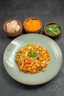 Salada saborosa de frente com ingredientes na dieta saudável de salada de mesa cinza