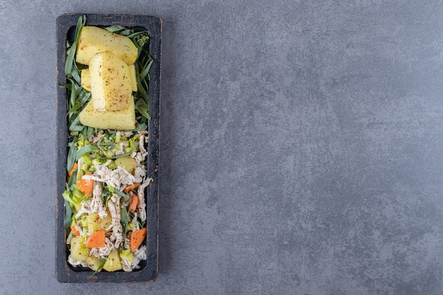 Salada saborosa e batatas cozidas na placa preta.