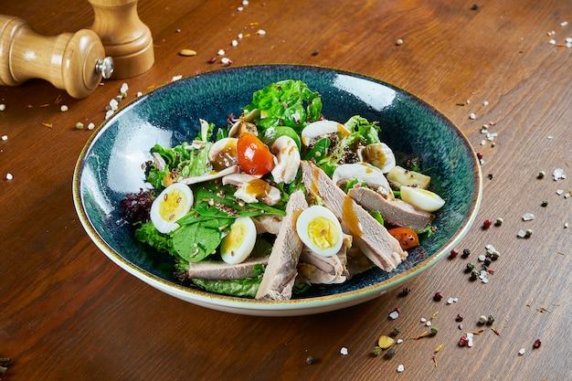 Salada saborosa e fresca com peito de pato, espinafre, quinoa, ovos de codorna e tomate cereja em uma tigela azul sobre uma mesa de madeira. nutrição de fitness saudável. fechar comida