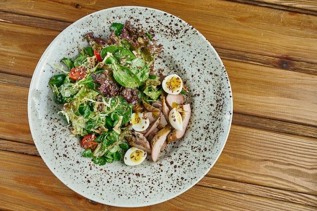 Salada saborosa e fresca com peito de pato, espinafre, quinoa, ovos de codorna e tomate cereja em uma tigela branca em uma mesa de madeira. nutrição de fitness saudável. fechar comida