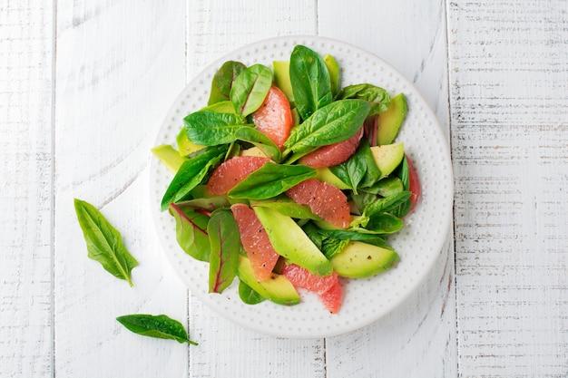 Salada saborosa útil de espinafre, acelga, abacate e toranja com azeite de oliva em fundo rústico de madeira branco.
