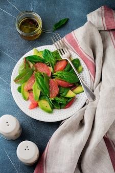Salada saborosa útil de espinafre, acelga, abacate e toranja com azeite de oliva em um fundo escuro de concreto velho.
