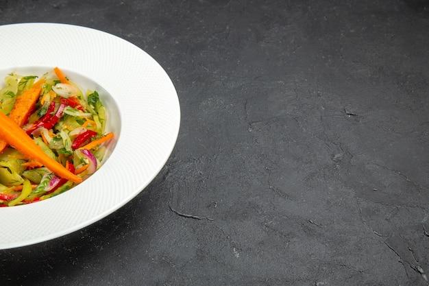 Salada salada de legumes no prato branco no fundo escuro