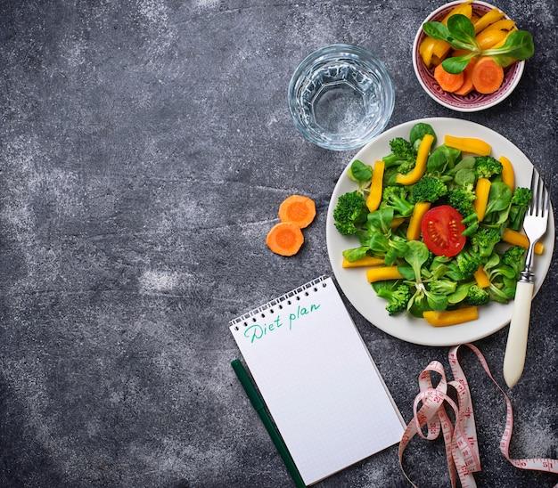 Salada saudável, água limpa e fita métrica.