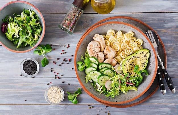 Salada saudável com frango, abacate, pepino, alface, rabanete e macarrão no escuro