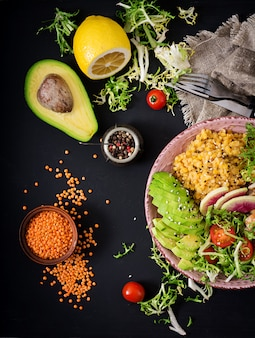 Salada saudável com frango, tomate, abacate, alface, rabanete melancia e lentilha na mesa escura.