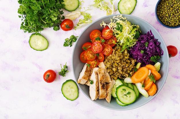 Salada saudável com frango, tomate, pepino, alface, cenoura, aipo, couve roxa e feijão mungo na mesa de luz.