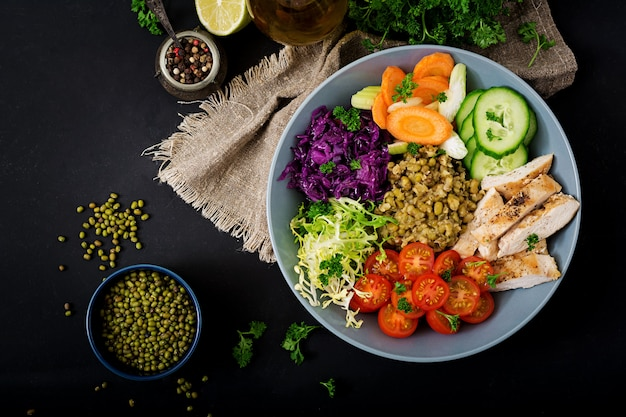Salada saudável com frango, tomate, pepino, alface, cenoura, aipo, couve roxa e feijão mungo na mesa escura.