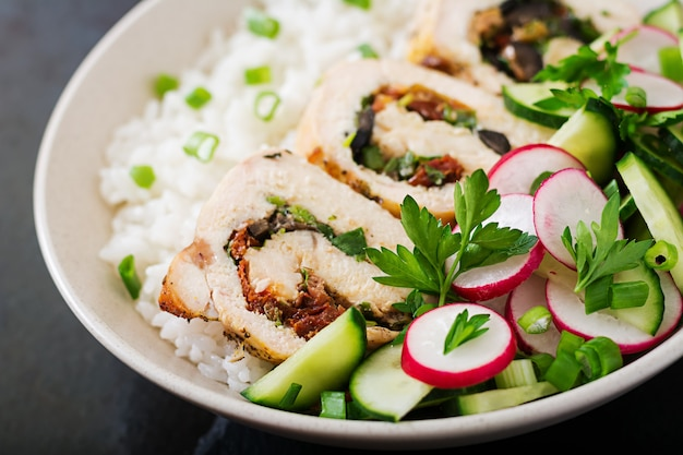 Salada saudável com rolos de frango, rabanetes, pepino, cebola verde e arroz. nutrição apropriada.