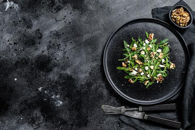Salada saudável com rúcula, queijo de cabra, nozes e molho vinagrete. fundo preto