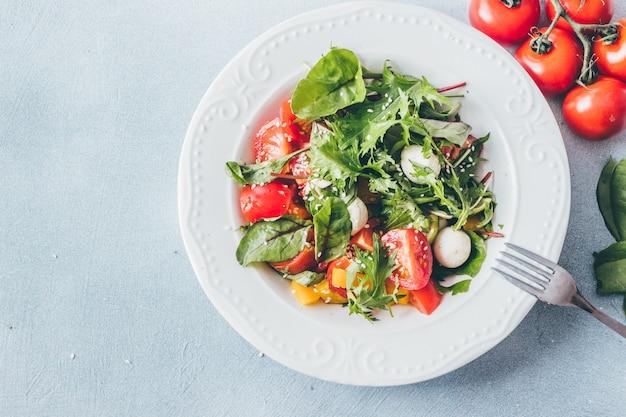 Salada saudável com tomate cereja, ervas e mussarela vista superior.