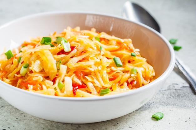 Salada saudável de couve e cenoura em uma tigela branca com cebolinha. conceito de comida fermentada saudável.